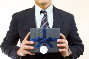 Businessman show gift box for you in studio